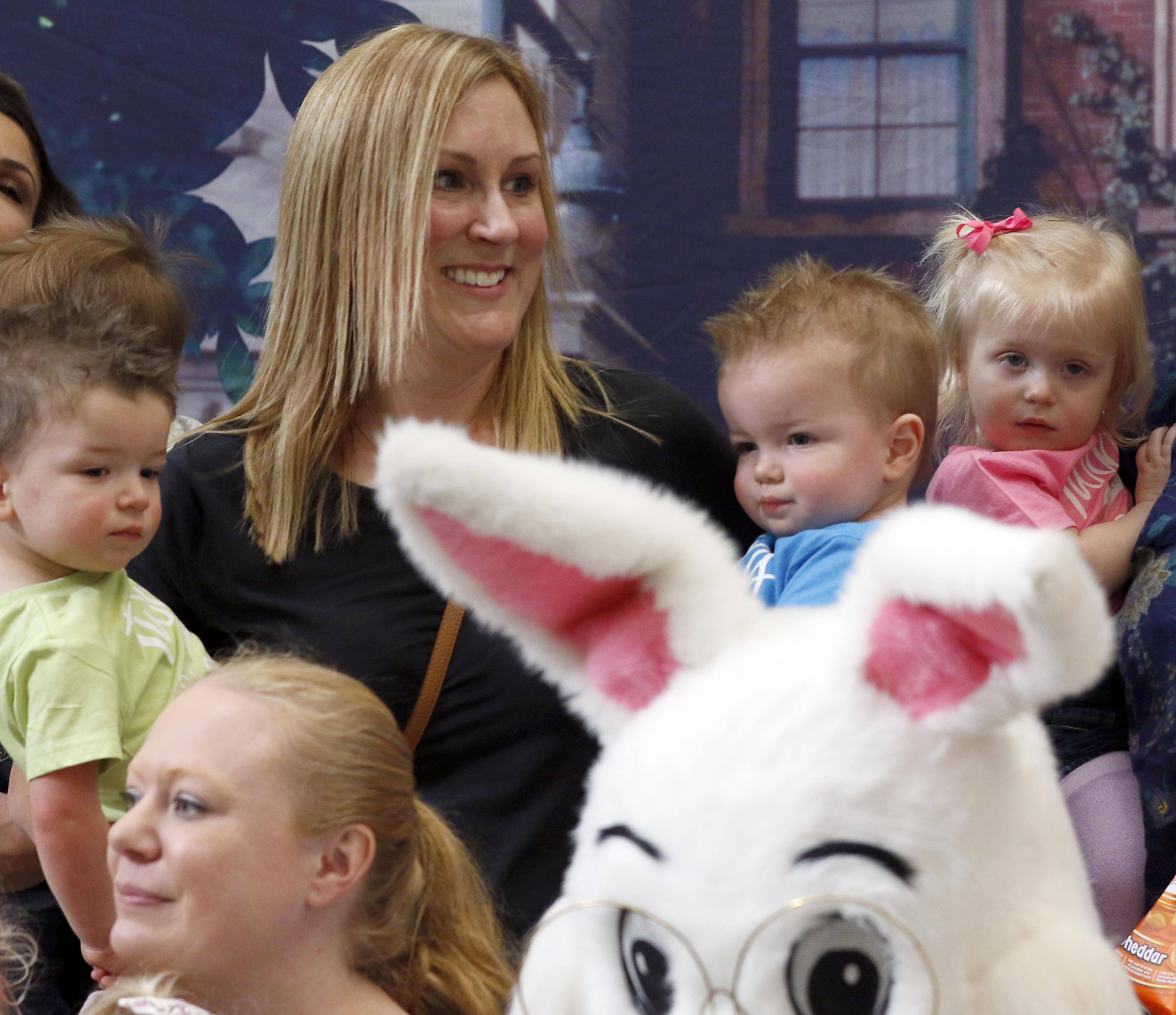 Stacy Kifer of Carol Stream holds her sons Kaleb, left, and Kobe, both 19 months, during a group photo with 17 other sets of twins and the Easter Bunny Tuesday at Woodfield Mall in Schaumburg.