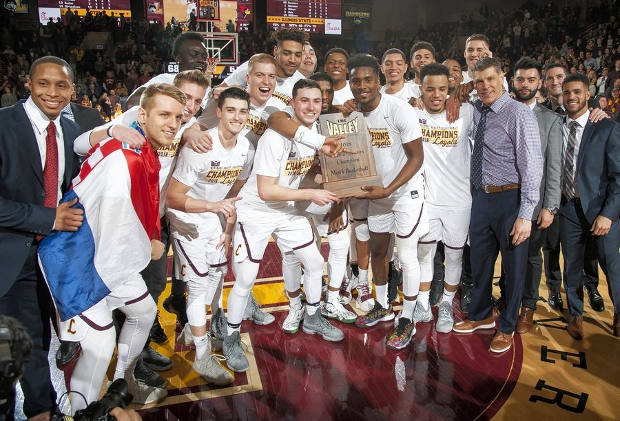 The Loyola Ramblers celebrate with the Missouri Valley Conference trophy after beating Southern Illinois on Feb. 21. Head coach Porter Moser, a Naperville native, is third from the right of the trophy.