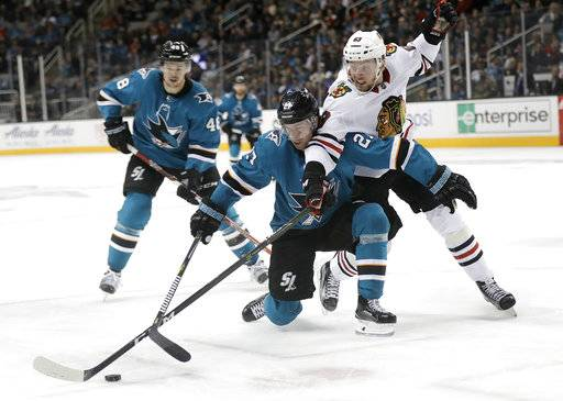 San Jose Sharks' Joonas Donskoi, center, is defended by Chicago Blackhawks' Carl Dahlstrom during the second period of an NHL hockey game Thursday, March 1, 2018, in San Jose, Calif.