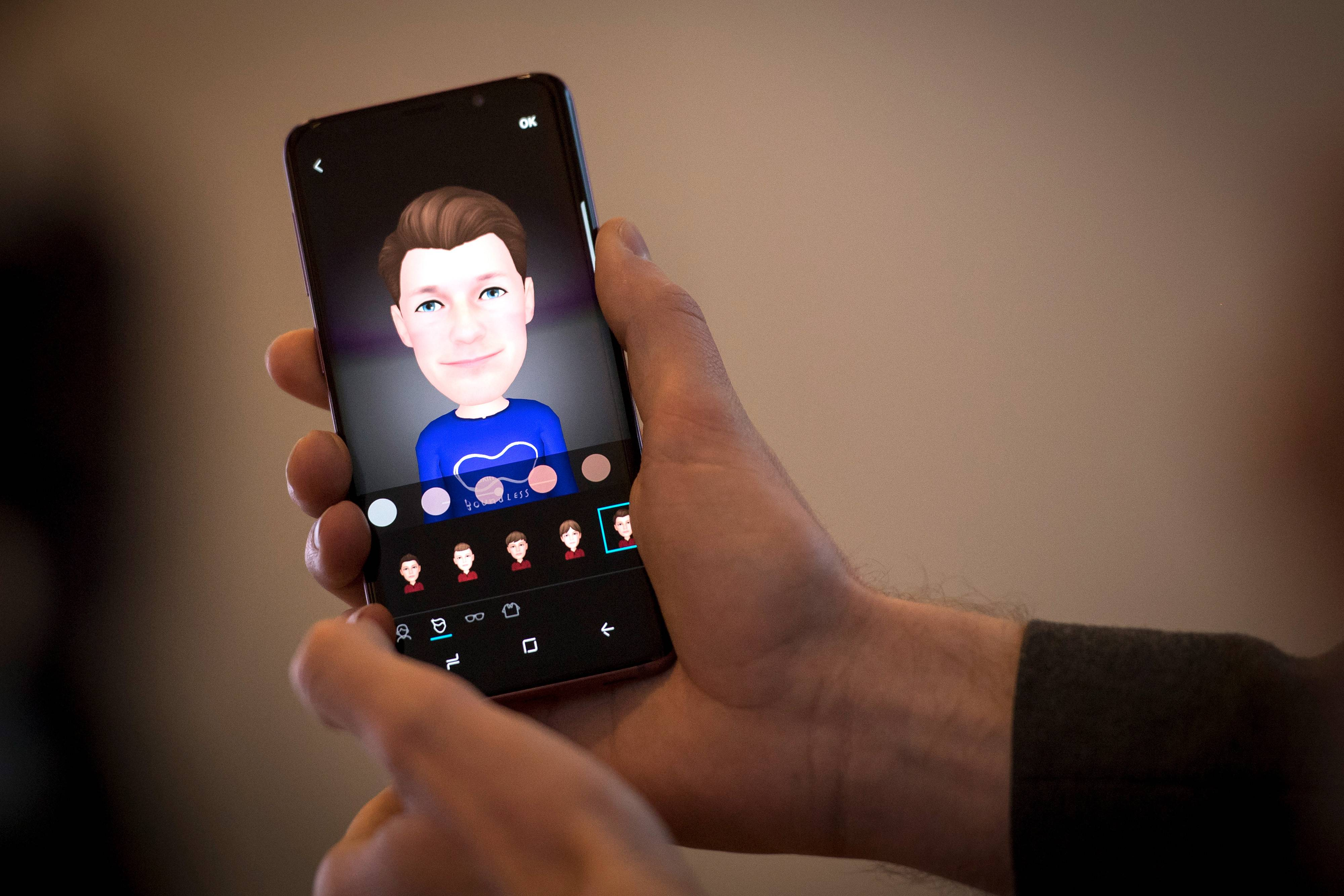 An attendee creates an emoji while holding a Samsung Electronics Galaxy S9 smartphone during the company's media event in San Francisco, California, U.S., on Feb. 16, 2018.