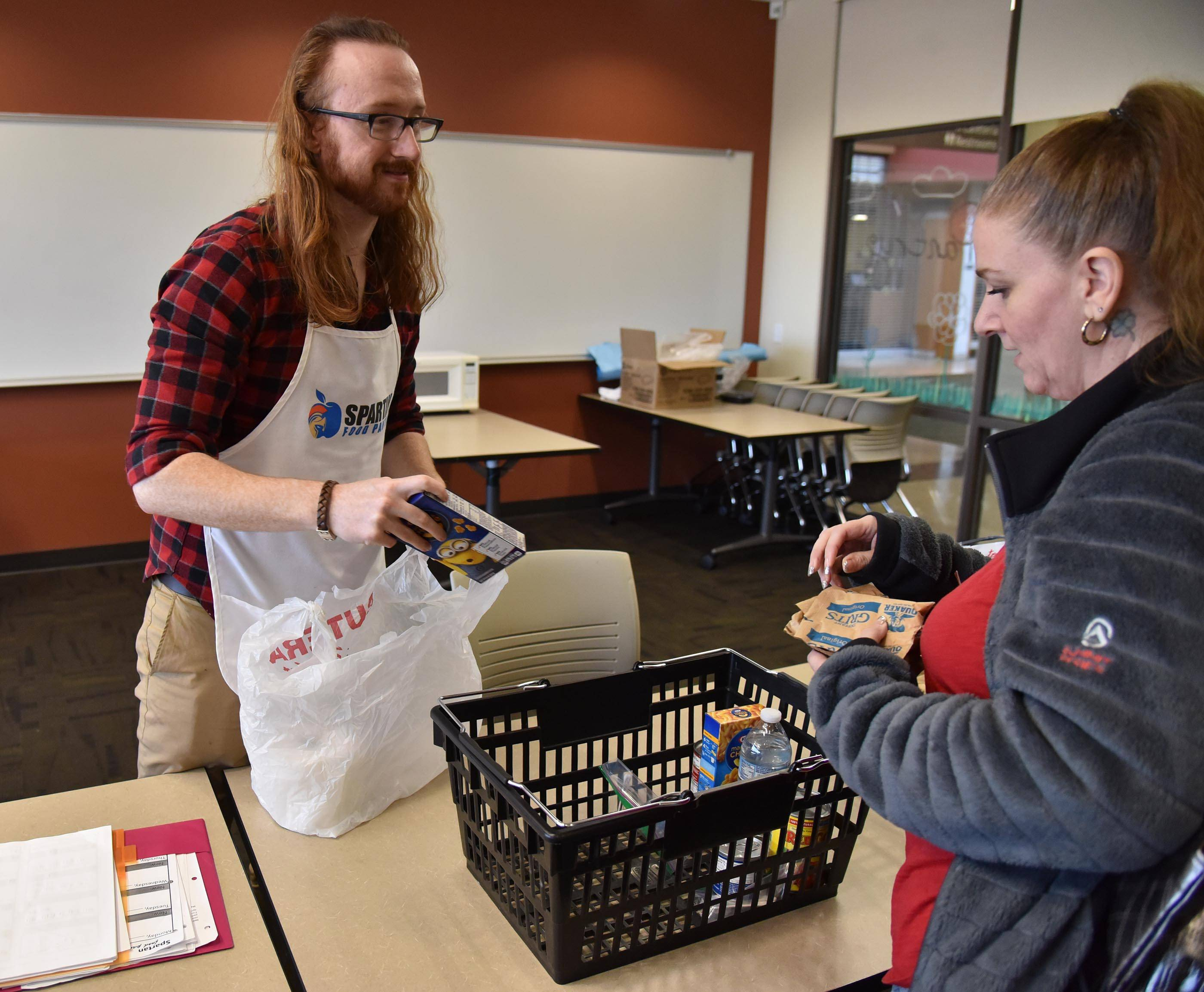 Andrew Pratt, co-officer of the Elgin Community College Spartan Food Pantry and a full-time student, helps ECC student Angela with her basket of goods. The pantry is one way suburban community colleges are trying to address food insecurity among students.