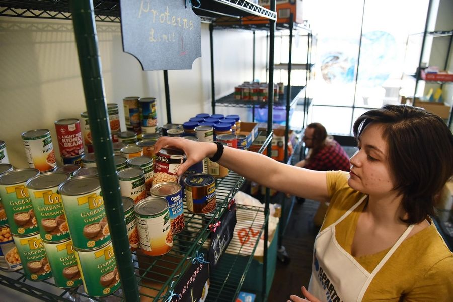 Stephanie Lagares and Andrew Pratt, both Elgin Community College students, check expiration dates on goods in the college food pantry.