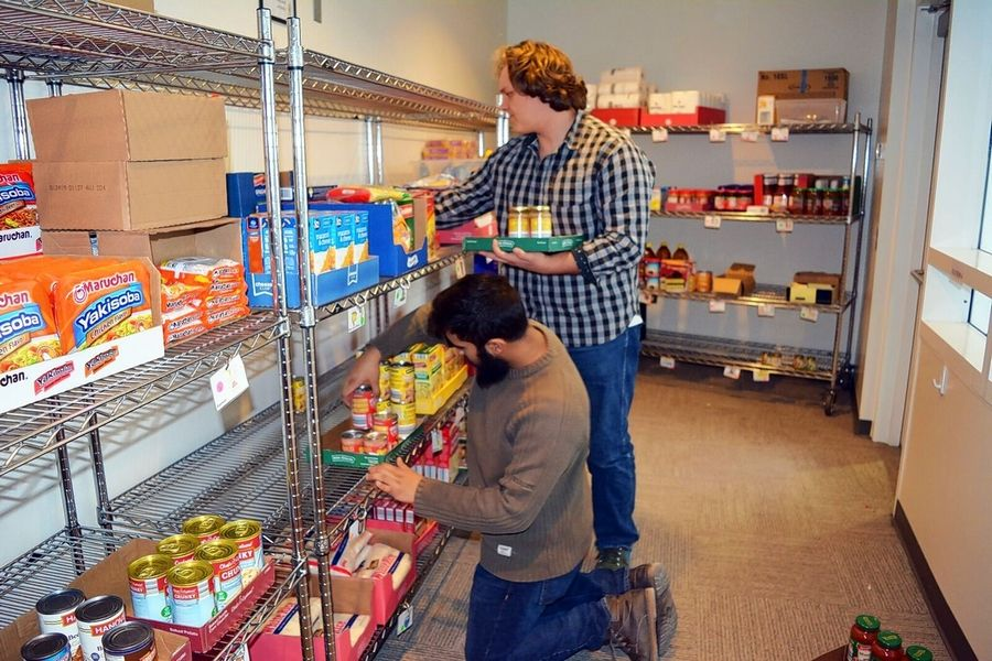 College of DuPage students Abbas Tayebal of Westmont, kneeling, and George Beck of Wheaton restock the campus Fuel Pantry, which helps students in need.