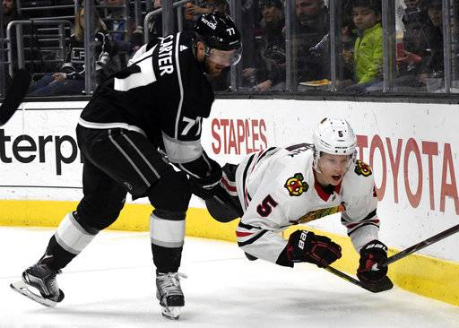 Chicago Blackhawks defenseman Connor Murphy (5) is knocked to the ice by Los Angeles Kings center Jeff Carter (77) during the second period of an NHL hockey game, Saturday, March 3, 2018, in Los Angeles.
