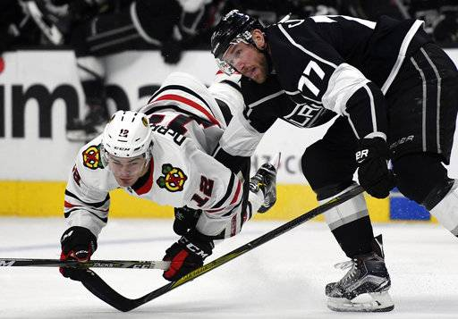 Chicago Blackhawks right wing Alex DeBrincat (12) hits the ice after a check by Los Angeles Kings center Jeff Carter (77) during the second period of an NHL hockey game, Saturday, March 3, 2018, in Los Angeles.