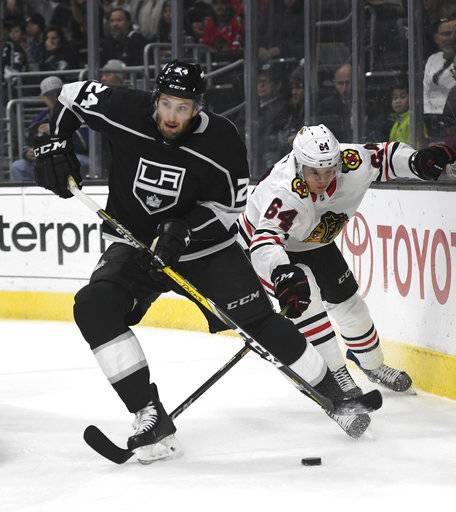 Los Angeles Kings defenseman Derek Forbort (24) tries to clear the puck as Chicago Blackhawks right wing David Kampf (64) pursues during the first period of an NHL hockey game, Saturday, March 3, 2018, in Los Angeles.