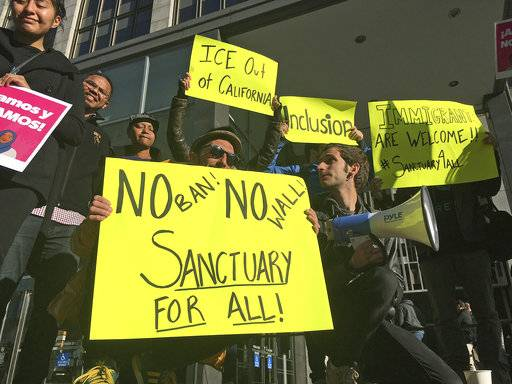FILE - In this April 14, 2017, file photo, protesters hold up signs outside a courthouse where a federal judge will hear arguments in the first lawsuit challenging President Donald Trump's executive order to withhold funding from communities that limit cooperation with immigration authorities in San Francisco. A federal judge in San Francisco will not immediately require the Trump administration to award California a law enforcement grant that the administration has held over concerns the state does not comply with immigration law. U.S. District Judge William Orrick on Monday, March 5, 2018, rejected the state's request for a preliminary injunction to turn over the money. (AP Photo/Haven Daley, File)