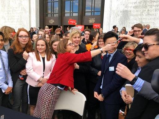 Oregon Gov. Kate Brown hands out one of the pens that she used to sign the first gun-control legislation signed into law in America since the Valentine's Day massacre at a Florida high school, on the steps of the state Capitol in Salem, Ore., Monday, March 5, 2018. Oregon high school students were among those who observed the signing. (AP Photo/Andrew Selsky)