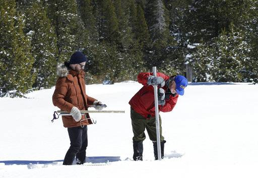 Frank Gehrke, chief of the California Cooperative Snow Surveys Program, for the Department of Water Resources, right, plunges the snow survey tube into the snow to check the depth of the snowpack during a supplemental snow survey Monday, March 5, 2018, near Echo Summit, Calif. The snow survey showed the snow pack at this location at 41.1 inches deep with a water content of 9.4 inches. Gehrke was accompanied by California Council of Science and Technology fellow, Keith Cialino (AP Photo/Rich Pedroncelli)