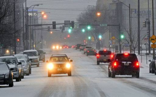 Traffic moves down a snow covered street in Bismarck, N.D., Monday, March 5, 2018, as snow falls. Freezing rain, heavy snow and strong winds are blowing into the northern Plains, impacting travel, schools and government offices. (Tom Stromme/The Bismarck Tribune via AP)