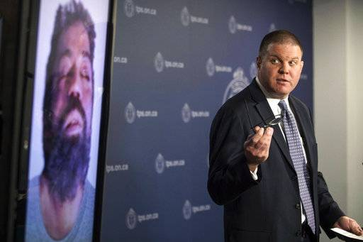 Det. Hank Idsinga, lead investigator in the case against Bruce McArthur, stands with a photo of an unidentified man, left, during a news conference at Toronto Police headquarters on Monday, March 5, 2018. Police are looking at unsolved missing person cases to determine if there are connections to McArthur, charged with multiple first-degree murders, and are running down tips that have come in from around the world. (Chris Young/The Canadian Press via AP)