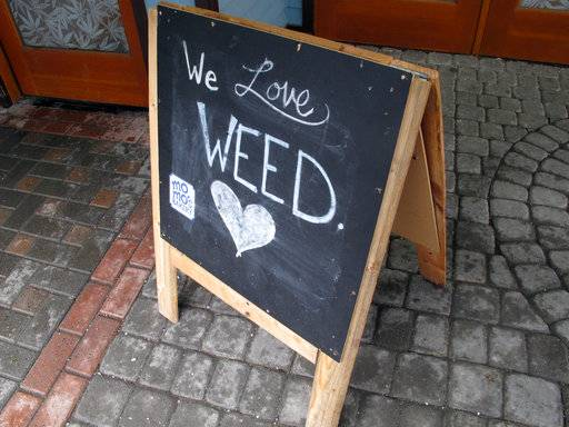 "In this Feb. 27, 2018, photo, a sign reading, ""We Love Weed"" stands outside a state-licensed marijuana shop in downtown Juneau, Alaska. Taking a cue from the fight over immigration, some states that have legalized marijuana are considering providing so-called sanctuary status for licensed pot businesses, hoping to protect the young industry from a shift in federal enforcement policy."