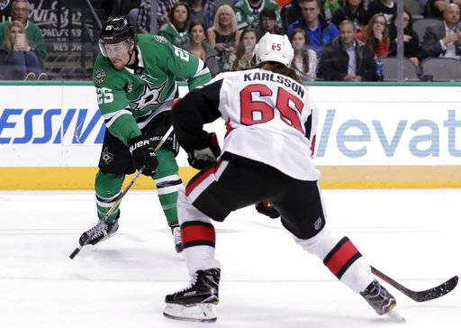 Dallas Stars right wing Brett Ritchie (25) advances the puck as Ottawa Senators defenseman Erik Karlsson (65) of Sweden defends in the first period of an NHL hockey game in Dallas, Monday, March 5, 2018. (AP Photo/Tony Gutierrez)