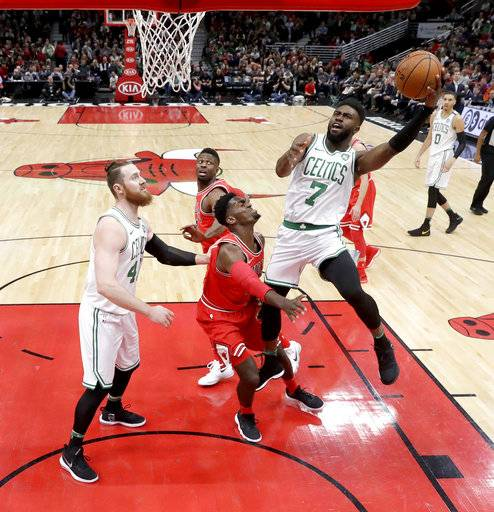 Boston Celtics' Jaylen Brown (7) shoots over Chicago Bulls' Bobby Portis as Aron Baynes, left, watches during the first half of an NBA basketball game Monday, March 5, 2018, in Chicago.