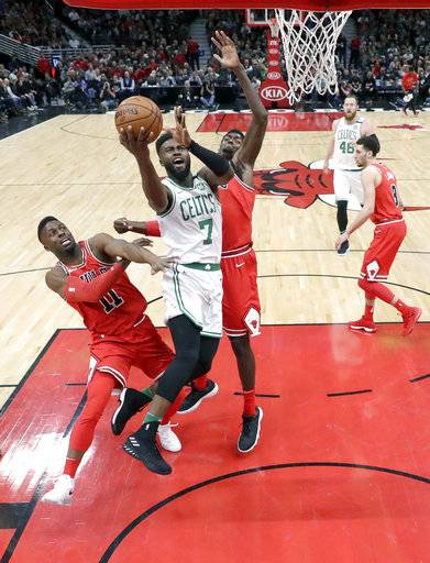 Boston Celtics' Jaylen Brown (7) drives to the basket past Chicago Bulls' David Nwaba (11) and Bobby Portis during the first half of an NBA basketball game Monday, March 5, 2018, in Chicago. The Bulls won 108-100.