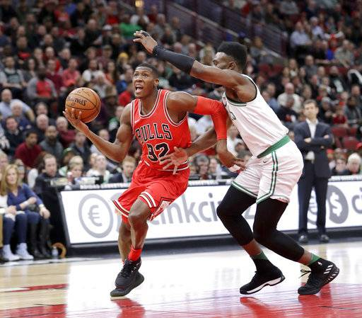 Chicago Bulls' Kris Dunn (32) drives past Boston Celtics' Jaylen Brown during the first half of an NBA basketball game Monday, March 5, 2018, in Chicago. The Bulls won 108-100.