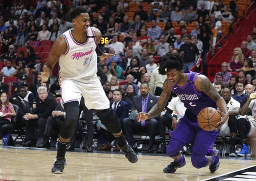 Phoenix Suns' Elfrid Payton (2) falls to the court as Miami Heat's Hassan Whiteside (21) defends during the first half of an NBA basketball game, Monday, March 5, 2018, in Miami. (AP Photo/Lynne Sladky)