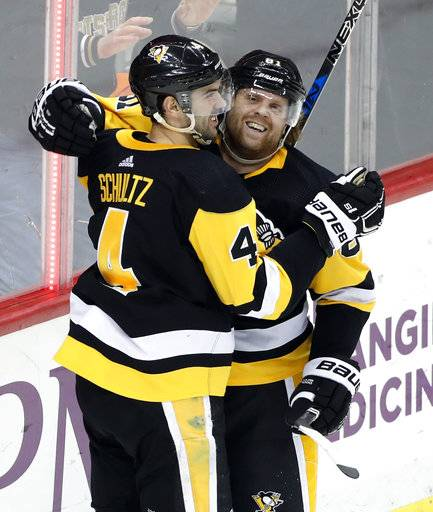 Pittsburgh Penguins' Justin Schultz (4) celebrates with Phil Kessel (81) after getting the game-winning goal in the overtime period of an NHL hockey game against the Calgary Flames in Pittsburgh, Monday, March 5, 2018. The Penguins won 4-3 in overtime. (AP Photo/Gene J. Puskar)