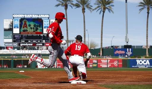 Cincinnati Reds first baseman Joey Votto (19) makes the catch at first base to get Los Angeles Angels' Shohei Ohtani, left, of Japan, out during the third inning of a spring training baseball game Monday, March 5, 2018, in Goodyear, Ariz. (AP Photo/Ross D. Franklin)