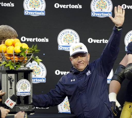 FILE- This Jan. 1, 2018 file photo shows Notre Dame head coach Brian Kelly celebrating with the championship trophy after defeating LSU 21-17 in the Citrus Bowl NCAA college football game in Orlando, Fla. Notre Dame won 21-17. Kelly has holes to fill on the offensive line and in the backfield and a competition at quarterback between Brandon Wimbush and Ian Book as the Irish, 10-3 and No. 11 in the final Associated Press poll in 2017, begin spring football drills Tuesday, March 6, 2018.