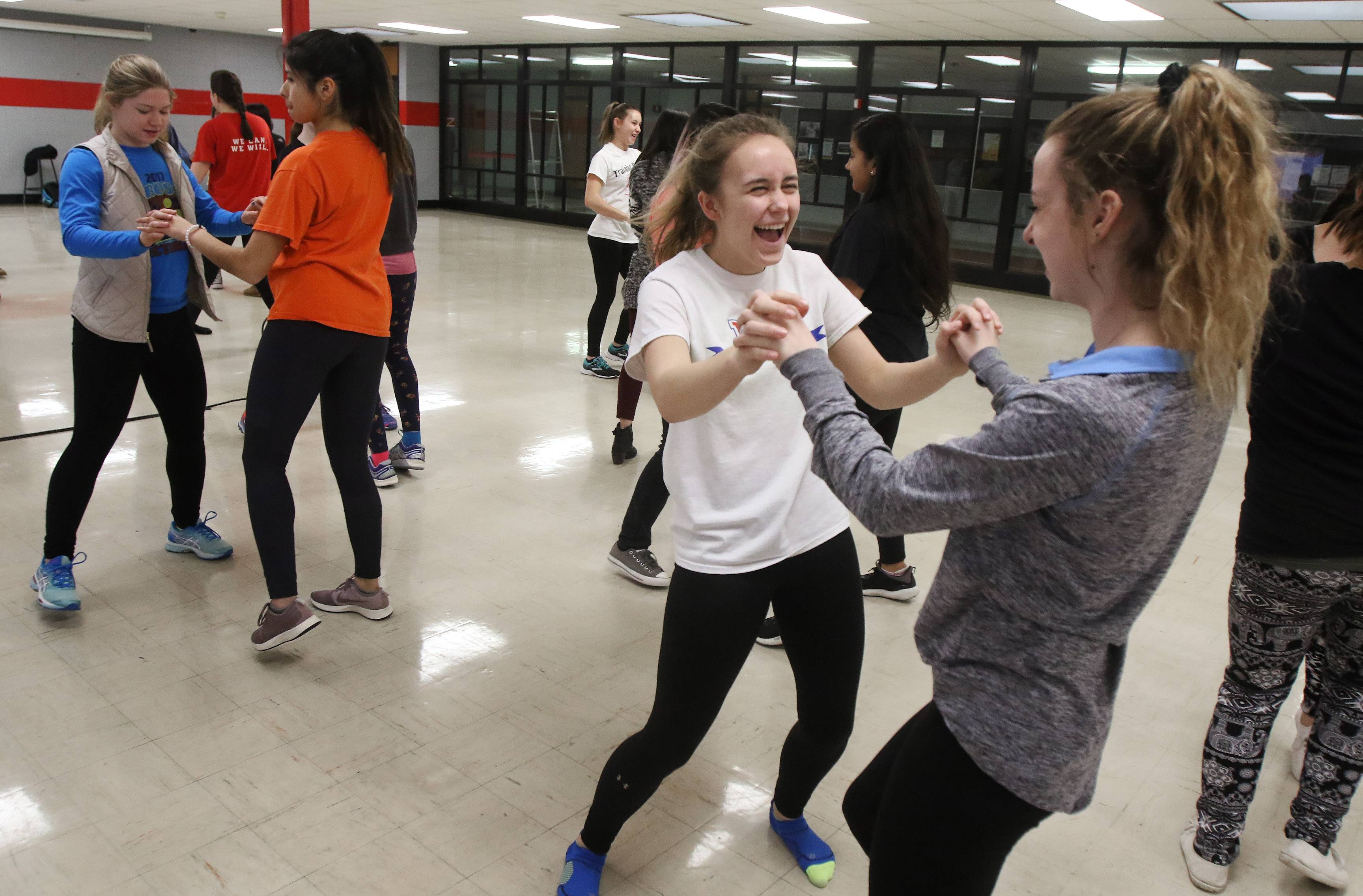 Junior Katie Miller, left, dances with junior Clarissa Wienckowski during the Latin dance workshop Tuesday at Mundelein High School. Members of the Puertas Latin Culture Club and the Student Leadership Organization provided lessons in preparation for the first Latin school dance on March 17.