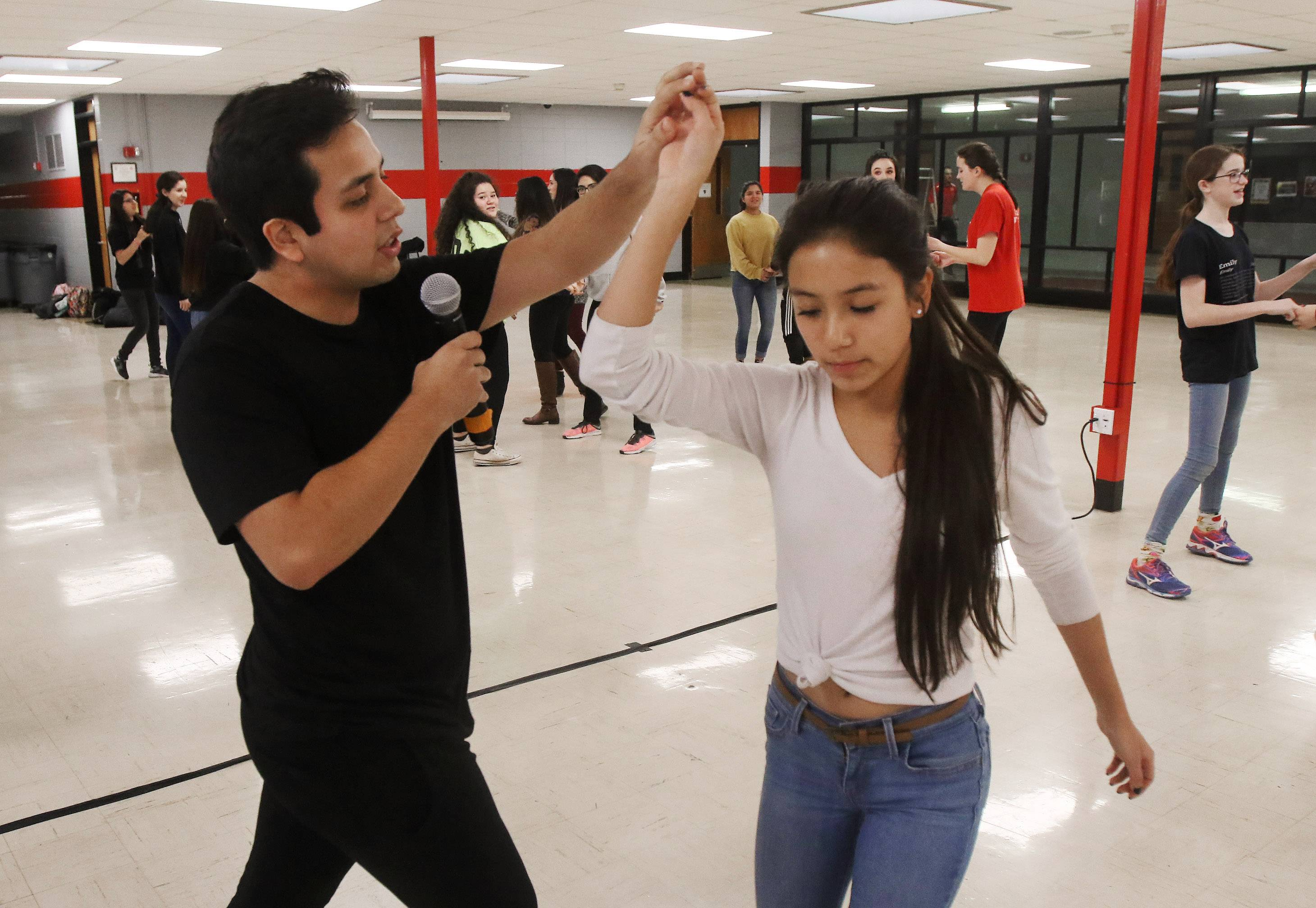 Former student Jason Jimenez demonstrates a dance move with his sister, Jeanelle, during the Latin dance workshop Tuesday at Mundelein High School. Members of the Puertas Latin Culture Club and the Student Leadership Organization provided lessons in preparation for the first Latin school dance on March 17.