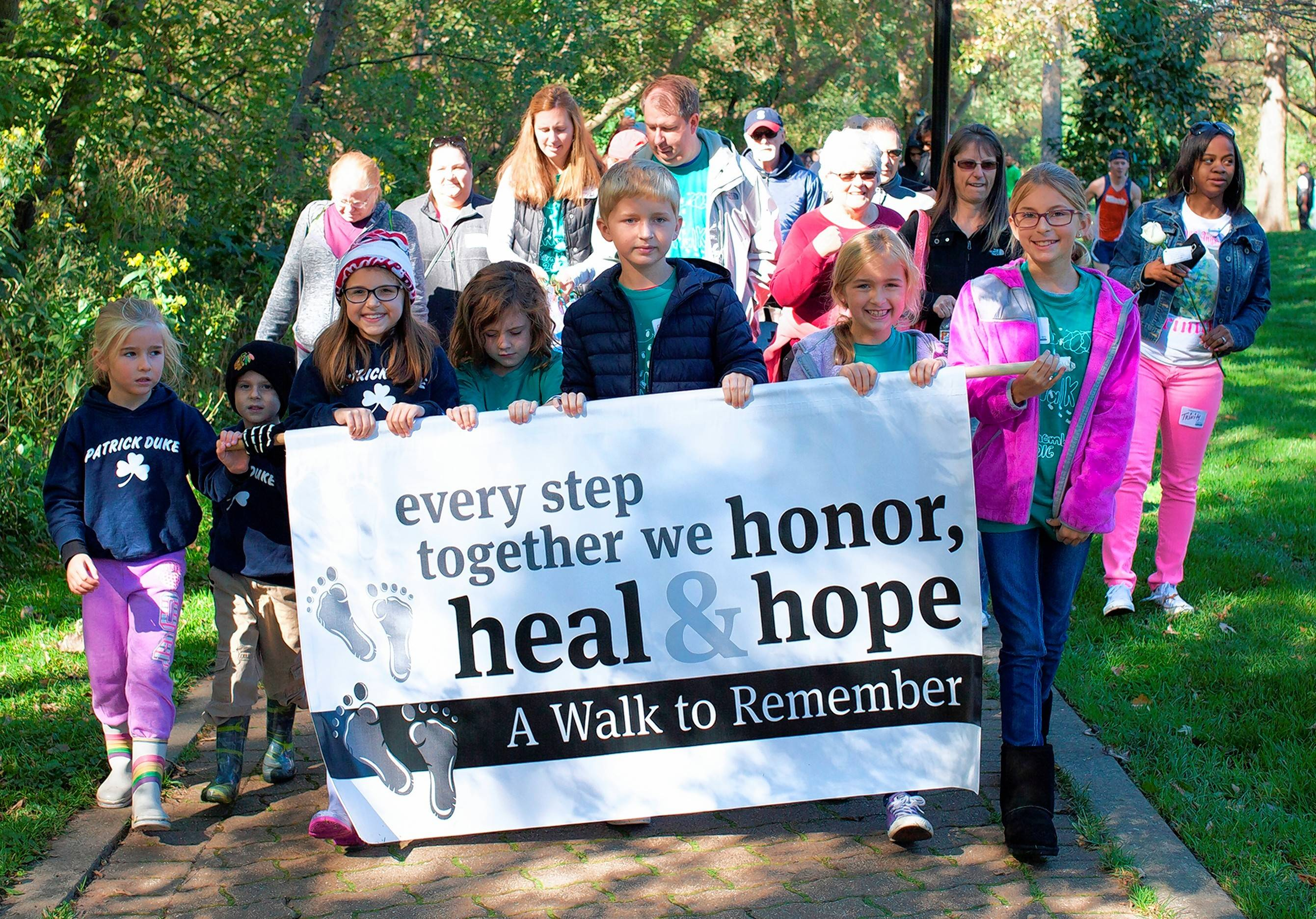 Carrying the banner to lead the 12th annual A Walk To Remember in 2016 were, from left, Kelsey, Danny and Reilly Fitzgerald of Naperville; Nora Mabrey of Naperville; and Ryan, Hannah and Hailey Mitchell of Aurora. The walk raises funds for the SHARE program, a support group for families who have lost a baby, at Edward Hospital in Naperville.