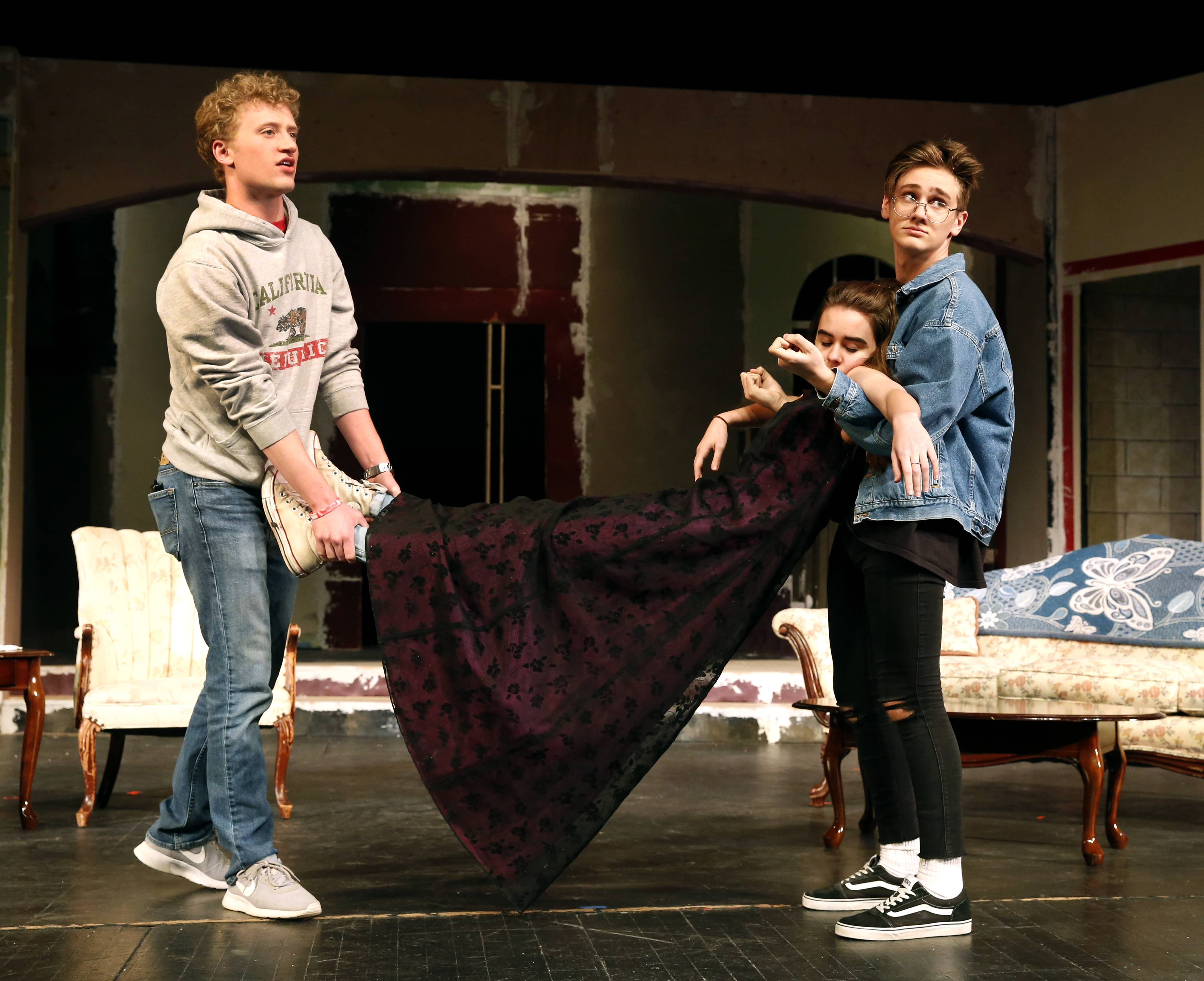"Alex Jech and Josh Anstrand carry Angelena Sizhelski as they rehearse a scene for Naperville Central High School's spring play, ""The Game's Afoot,"" a whodunit set during the Christmas holidays in the 1930s."