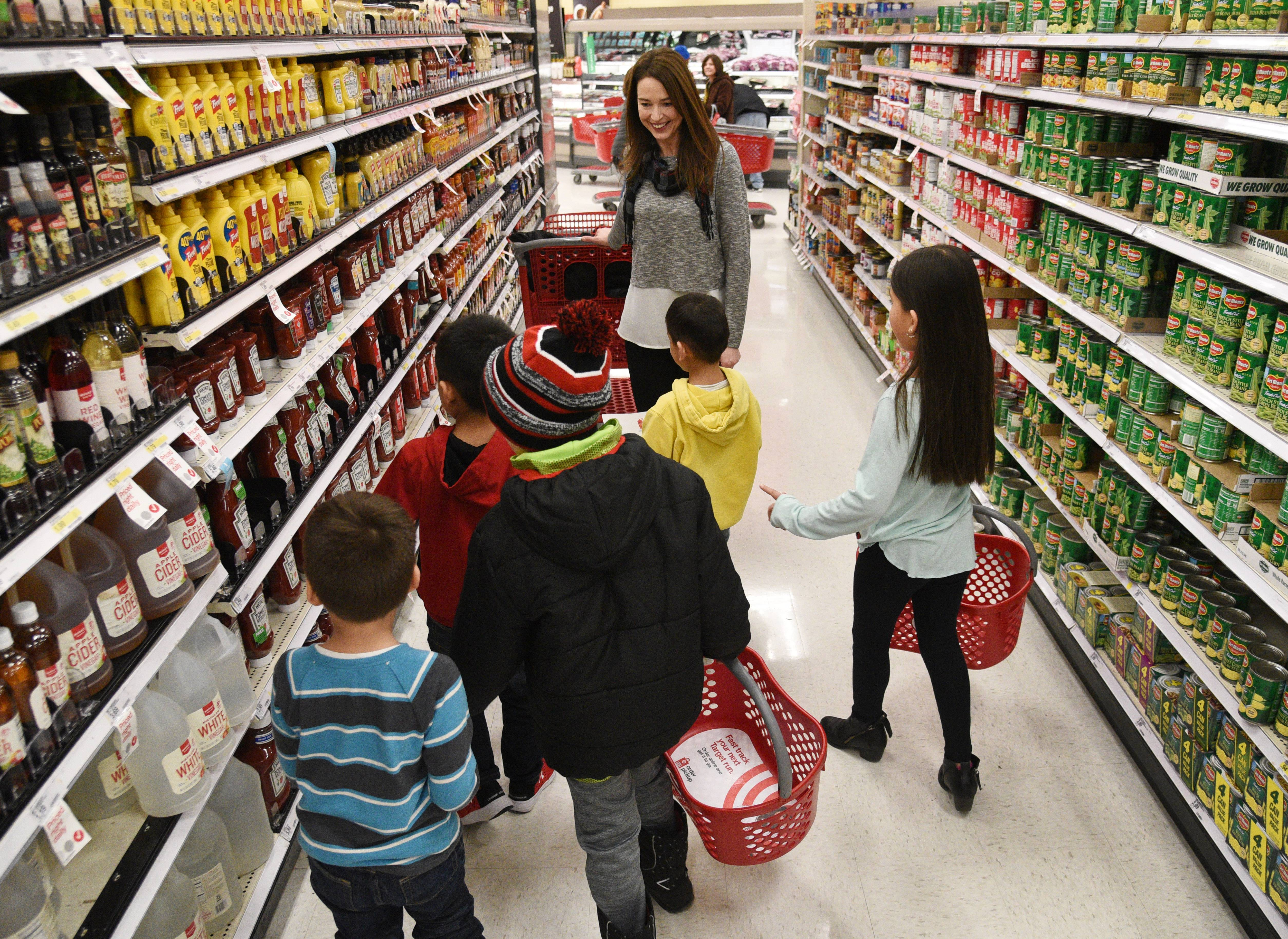 Fremont Elementary School kindergarten teacher Lisa Listi shops with a groups of District 79 students Wednesday at the Mundelein Target store. Teachers, students and parents are teaming up to buy items for the Fremont Township Food Pantry.