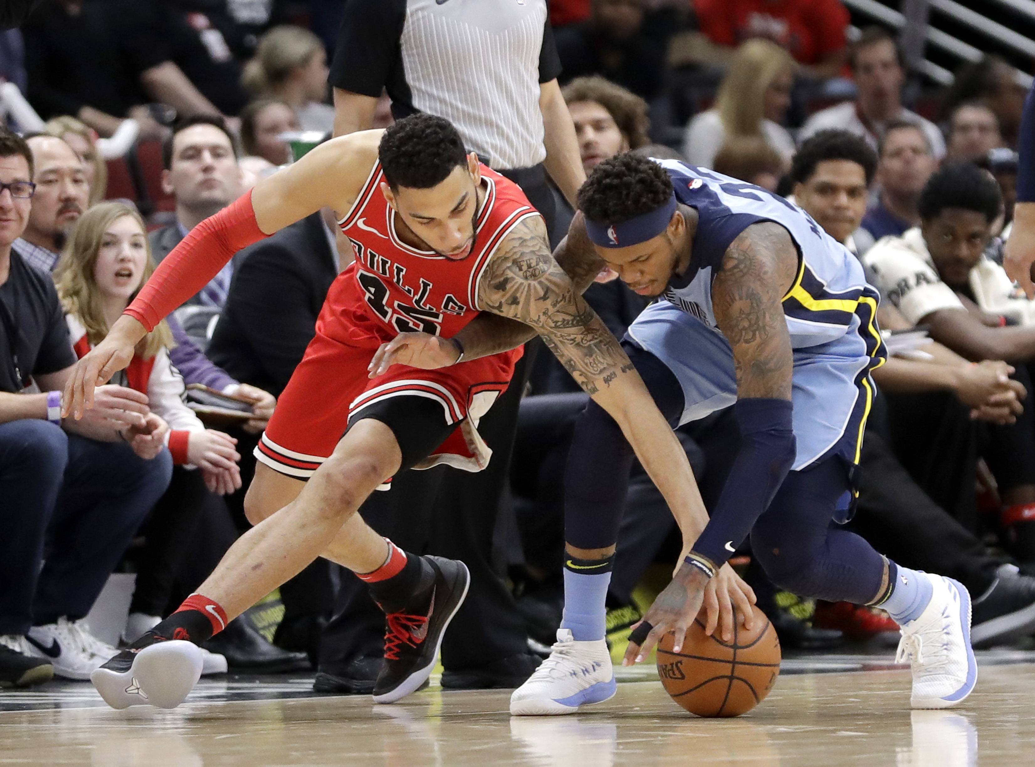 Chicago Bulls' Denzel Valentine, left, and Memphis Grizzlies' Ben McLemore, right, battle for a loose ball during the second half of an NBA basketball game Wednesday, March 7, 2018, in Chicago. The Bulls won 119-110.