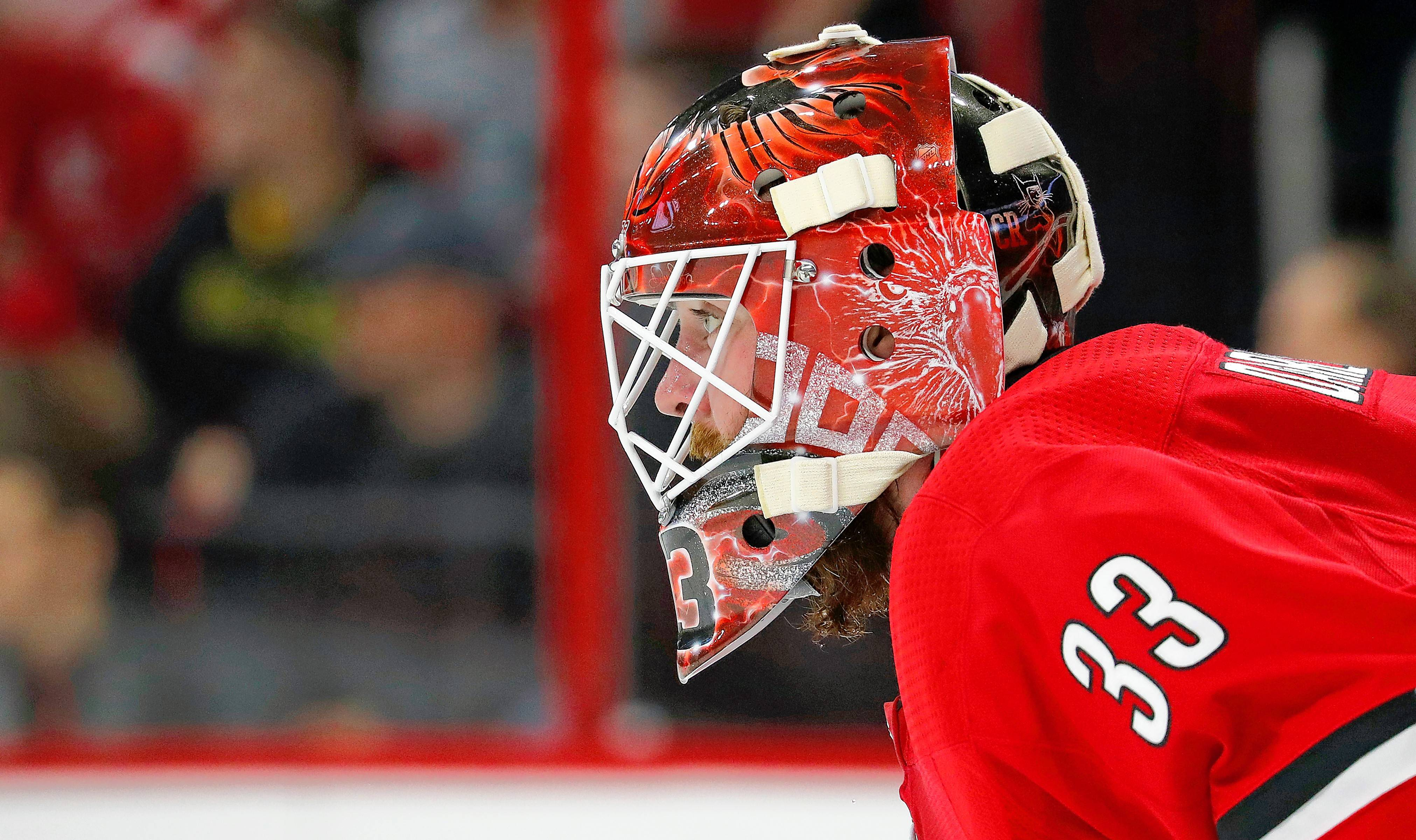 Carolina Hurricanes goaltender Scott Darling (33) eyes the puck against the Detroit Red Wings during the first period of an NHL hockey game, Friday, Feb. 2, 2018, in Raleigh, N.C.