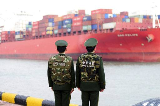 Chinese border police officers watch the arrival of a container ship at a port in Qingdao in eastern China's Shandong province, Thursday, March 8, 2018. China's exports in February surged 44.5 percent over a year earlier while its politically sensitive trade surplus widened amid mounting tension with Washington. (Chinatopix via AP)