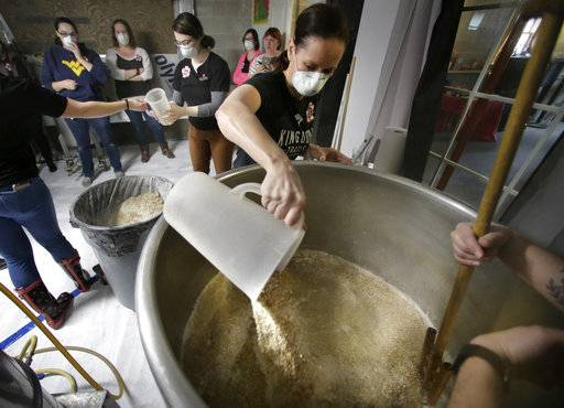 In this Sunday, March 4, 2018, photo, Elizabeth Bove, of Woodstock, Conn., pours grain into a mash mixture while helping brew a batch of beer at Black Pond Brews brewery, in Danielson, Conn. The brewery hosted homebrewers and beer enthusiasts for a Pink Boots Society event in honor of International Women's Day, on March 8. Thousands of women in the beer business and homebrewers in a number of countries are brewing together around that day as a way to raise the profile of women in a male-dominated industry.