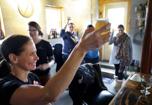 In this Sunday, March 4, 2018, photo, Elizabeth Bove, of Woodstock, Conn., left, joins with others as they raise their glasses in a toast after helping brew a batch of beer at Black Pond Brews brewery, in Danielson, Conn. The brewery hosted homebrewers and beer enthusiasts for a Pink Boots Society event in honor of International Women's Day, on March 8. Thousands of women in the beer business and homebrewers in a number of countries are brewing together around that day as a way to raise the profile of women in a male-dominated industry.