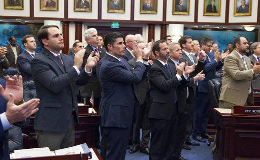 School safety bill Florida House sponsor Rep. Jose Oliva, second from left, (R-Hialeah) is joined by the House members in applauding Andrew Pollack, father of 18 year-old school shooting victim Meadow Pollack, after a school safety bill passed the House 67-50 at the Florida Capital in Tallahassee, Fla., Wednesday March 7, 2018.