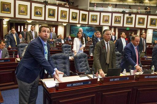 Florida Rep. Jason Brodeur, left, (R- Sanford), watches the vote board as he votes on the school safety bill which passed the House 67-50 at the Florida Capital in Tallahassee, Fla., Wednesday, March 7, 2018.