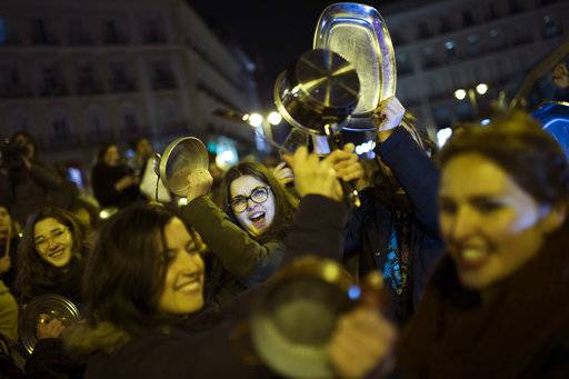 Women bang pots and pans as shooting slogans during a protest marking the beginning of a 24-hour women strike at the Sol square in Madrid, early Thursday, March 8, 2018. Women in Spain have been called for a 24-hour feminist strike in their workplaces and also stop doing duties at home during the International Women's Day.