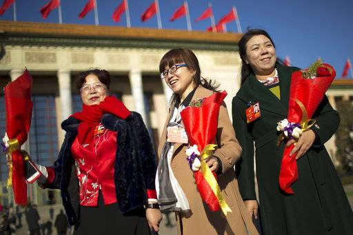 Delegates hold flower bouquets for International Women's Day as they arrive for a plenary session of the Chinese People's Political Consultative Conference (CPPCC) at the Great Hall of the People in Beijing, Thursday, March 8, 2018. Students at China's prestigious Tsinghua University are celebrating International Women's Day with banners making light of a proposed constitutional amendment to scrap term limits for the country's president.