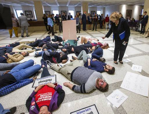 Florida Rep. Janet Cruz (D-Tampa) walks around a group of 20 college students and activists as they stage a die-in on the 4th floor rotunda between the House and Senate chambers while the House takes up the school safety bill at the Florida Capital in Tallahassee, Fla., Tuesday March 6, 2018.