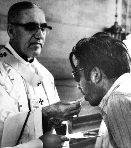 FILE - Archbishop Oscar Arnulfo-Romero offers the host wafer during the communion rite to a member of the congregation during a church mass in San Salvador, El Salvador on Jan. 13, 1980. Pope Francis has cleared the way for slain Salvadoran Archbishop Oscar Romero to be made a saint, declaring that a churchman who stood up for the poorest of the poor in the face of right-wing oppression should be a model for Catholics today.