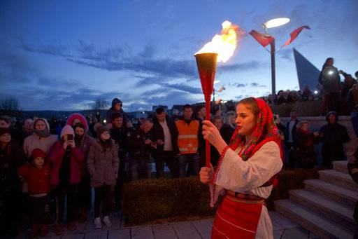 "A Kosovo Albanian woman in national costume holds a torch during a bonfire ceremony ""Night of the Fires"" in the village of Prekaz, Kosovo on Wednesday, March 7, 2017. Kosovo Liberation Army (KLA) commander Adem Jashari was killed along with 45 members of his family by Serb forces during the Kosovo war in the village of Prekaz in 1998. Every year hundreds of people gather to commemorate the event with a bonfire ceremony in the village."