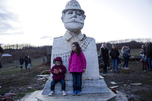 "Kosovo Albanian children in national costumes stand in front of the statue of Adem Jashari during a bonfire ceremony ""Night of the Fires"" in the village of Prekaz, Kosovo on Wednesday, March 7, 2017. Kosovo Liberation Army (KLA) commander Adem Jashari was killed along with 45 members of his family by Serb forces during the Kosovo war in the village of Prekaz in 1998. Every year hundreds of people gather to commemorate the event with a bonfire ceremony in the village."