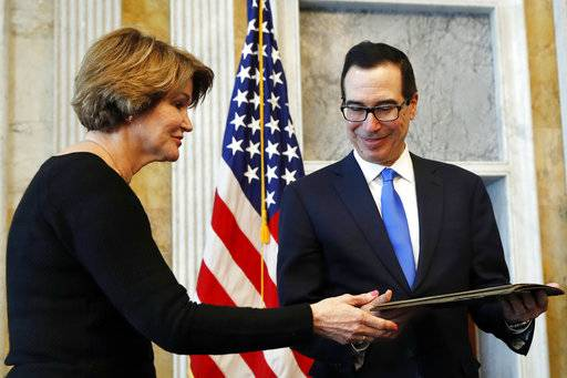 Bay Buchanan, with the National Collector's Mint, left, hands a letter from 1861 to Treasury Secretary Steven Mnuchin, right, as he accepts the Civil War-era document written by the 24th Treasury Secretary John Adams Dix on behalf of the Treasury Department, during a ceremony at the Treasury, Wednesday, March 7, 2018.