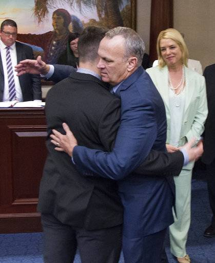 Florida Speaker of the House, Rep. Richard Corcoran, center, (R-Lutz) hugs Hunter Pollack, brother of high school shooting victim Meadow Pollack, after the school safety bill passed the House 67-50 at the Florida Capital in Tallahassee, Fla., Wednesday March 7, 2018. Florida Attorney General Pam Bondi, right, looks on.
