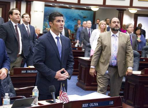 Florida House bill sponsor Rep. Jose Oliva, center, (R- Hialeah), watches the vote board at the Florida Capital in Tallahassee, Fla., Wednesday March 7, 2018. The Florida House has passed a school safety bill that includes new restrictions on rifle sales and a program to arm some teachers. The House voted 67-50 Wednesday on a bill that's a response to the Feb. 14 shooting at a high school that killed 17 people.