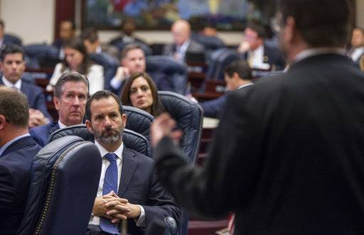 Florida Rep. Michael Bileca (R-Miami), center left, listens as Rep. Chris Latvala (R-Clearwater) speak on the school safety bill in the House chamber at the Florida Capital in Tallahassee, Fla., Wednesday, March 7, 2018.