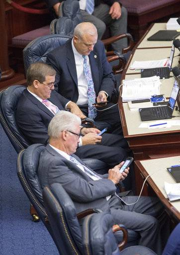 Front to back, Rep. Bobby Payne (R-Palatka), Rep. Clay Yarborough (R- Jacksonville) and Rep. Rick Roth (R- Palm Beach) look at their mobile devices on the House floor as the school safety debate moves into the afternoon at the Florida Capital in Tallahassee, Fla., Wednesday March 7, 2018.