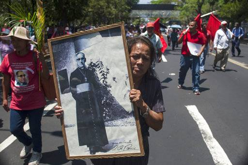 FILE -- In this March, 24, 2015 file photo, Maria del Pilar Perdomo, 58, holds up a framed portrait of slain Archbishop of San Salvador, Oscar Arnulfo Romero, during a procession to mark the 35th anniversary of his assassination in San Salvador, El Salvador. Pope Francis has cleared the way for slain Salvadoran Archbishop Oscar Romero to be made a saint, declaring that a churchman who stood up for the poorest of the poor in the face of right-wing oppression should be a model for Catholics today.