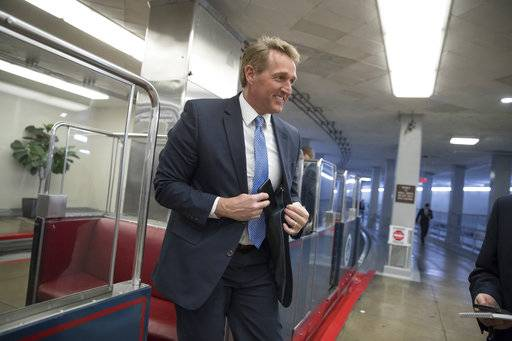 Sen. Jeff Flake, R-Ariz., arrives for a procedural vote as the Senate moves to pass legislation that would roll back some of the safeguards Congress put into place after a financial crisis rocked the nation's economy ten years ago, at the Capitol in Washington, Tuesday, March 6, 2018.