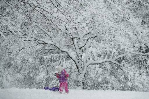 A young girl plays in the snow during a winter storm, Wednesday, March 7, 2018, in Marple Township, Pa.